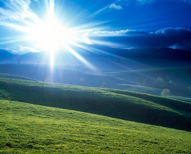 Sun burst over green rolling hill