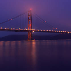 Suspension bridge lit up at dawn viewed from fishing pier, Golden Gate Bridge, San Francisco Bay, San Francisco, California, USA