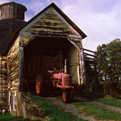 Tractor parked inside of a round barn, Vermont, USA