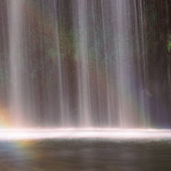 Rainbow formed in front of waterfall in a forest, California, USA