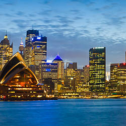Opera house and buildings lit up at dusk, Sydney Opera House, Sydney Harbor, Sydney, New South Wales, Australia