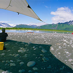Tourists sitting at the campsite near a lake, Bear Glacier Lake, Kenai Fjords National Park, Alaska, USA