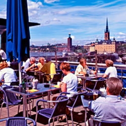 People in a restaurant with the city skyline in the background, Eken Restaurant, Lake Malaren, Gamla Stan, Stockholm, Sweden
