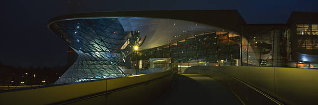 Commercial buildings lit up at night, BMW Welt, Munich, Bavaria, Germany