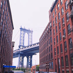 Low angle view of a suspension bridge viewed through buildings, Manhattan Bridge, Brooklyn, New York City, New York State, USA