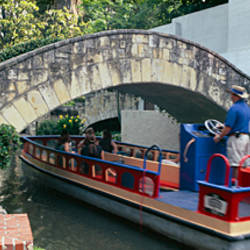 Boat passing under a bridge, Arneson River Theater, Arneson River, San Antonio, Texas, USA