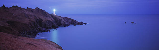 Lighthouse lit up at dusk, Start Point Lighthouse, Devon, England