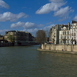 Buildings along a river with a cathedral in the background, Notre Dame, Paris, Ile-De-France, France