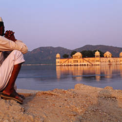 Side profile of two men sitting at a lakeside with a palace in the background, Jal Mahal, Jaipur, Rajasthan, India