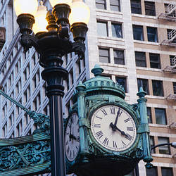 Close-up of a clock beside a lamppost, Marshall Field Clock, Chicago, Illinois, USA