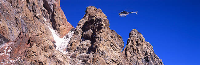 Low angle view of a helicopter flying over mountains, Grand Teton National Park, Wyoming, USA