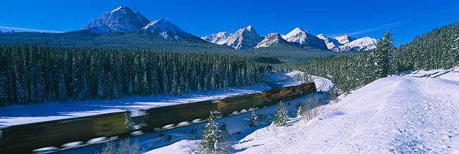 Train moving on a railroad track with a mountain range in the background, Banff National Park, Alberta, Canada