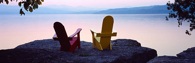 Red and Yellow Adirondack chairs on a rock near a lake, Champlain Lake, Vermont, USA