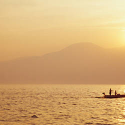 Silhouette of a fishing boat in a lake at sunrise, Lake Garda, Italy