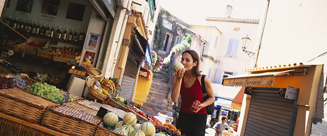 Young woman smelling a melon in a market, St. Tropez, France