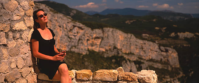 Young woman sitting on a wall and holding a glass of wine, Provence, France