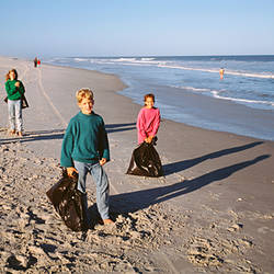 Group of children carrying garbage bags and walking on the beach