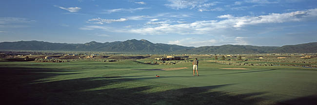 Rear view of a man playing golf, Taos, New Mexico, USA
