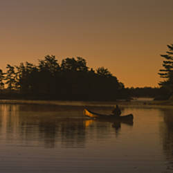 Silhouette of a person in a canoe on a lake, Kejimkujik Lake, Kejimkujik National Park, Nova Scotia, Canada