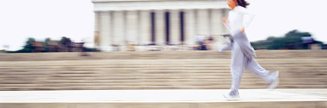 Side profile of a young woman jogging in front of a memorial building, Lincoln Memorial, Washington DC, USA