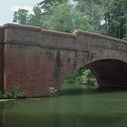 USA, North Carolina, Asheville, View of a red brick arched bridge over river