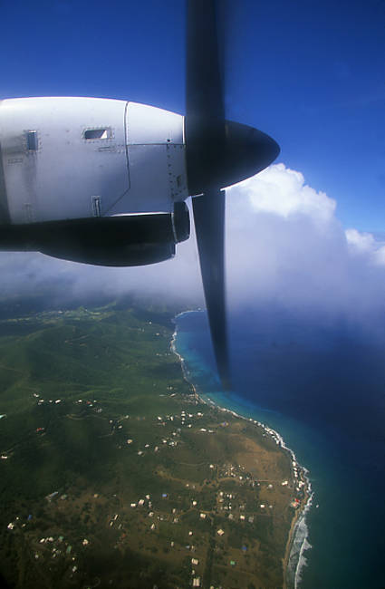 Propeller airplane in flight with an island in the background, Beef Island, Tortola, British Virgin Islands