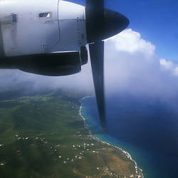 Propeller airplane in flight with an island in the background, Beef Island, Tortola, British Virgin Islands