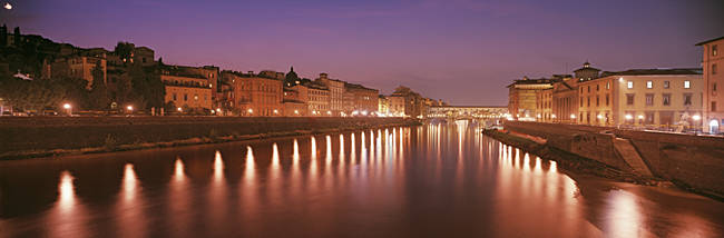 Italy, Florence, Arno River, Panoramic view of building along a lit up river