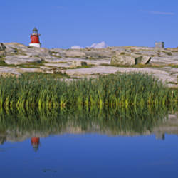 Reflection Of A Lighthouse And A House On The Water, Bohuslan, Sweden