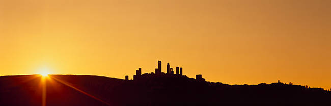 Silhouette of a town on a hill at sunset, San Gimignano, Tuscany, Italy